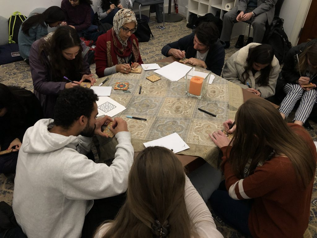 Students sitting around a table creating mosaic tiles