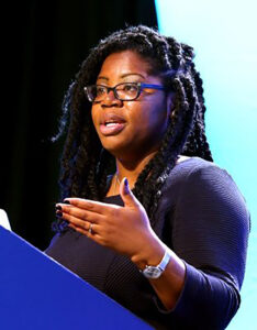 Dr. Shannen Dee Williams standing at a lectern Delivering a talk