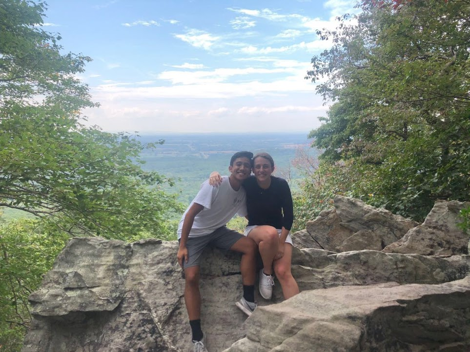 Two students sitting on a rock with mountains as a backdrop.