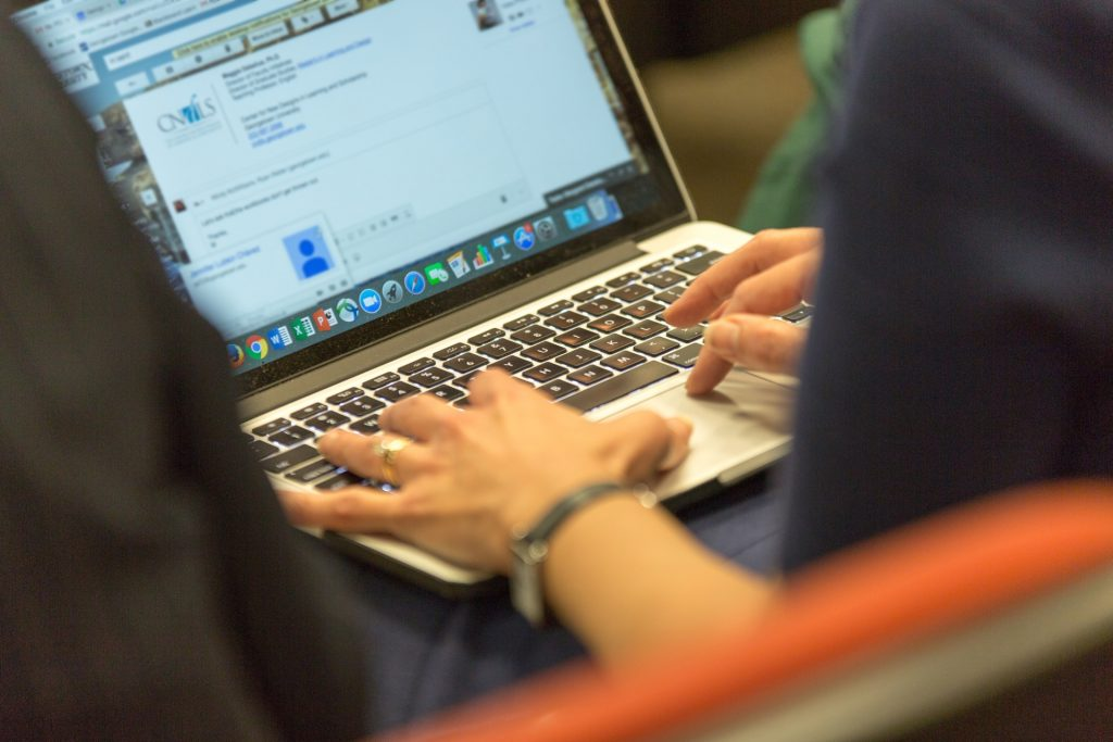 We see a close-up of the screen of a woman's laptop and the woman's hands as she types an email.