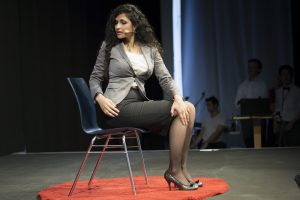 Renu, sitting in a chair doing a yoga pose, as part of her TEDx Talk