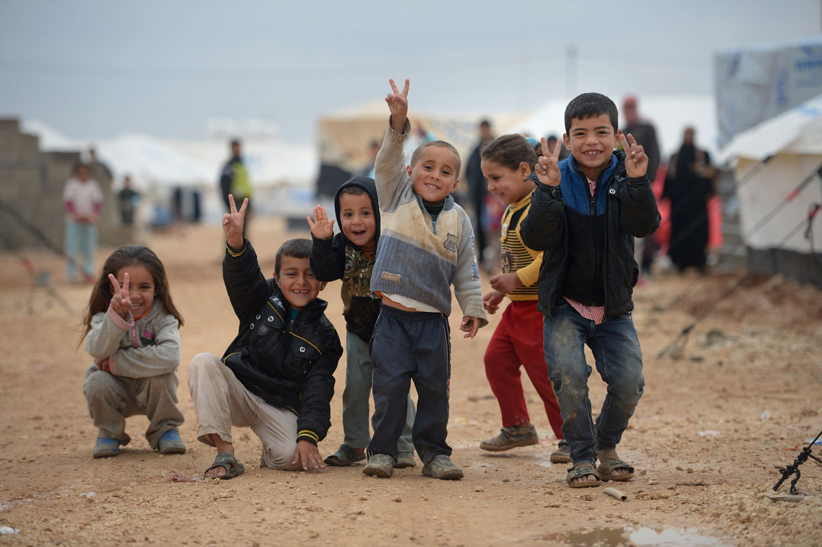 ZA'ATARI, JORDAN - FEBRUARY 01:  Children pose for a picture as Syrian refugees go about their daily business in the Za'atari refugee camp on February 1, 2013 in Za'atari, Jordan. Record numbers of refugees are fleeing the violence and bombings in Syria to cross the borders to safety in northern Jordan and overwhelming the Za'atari camp. The Jordanian government are appealing for help with the influx of refugees as they struggle to cope with the sheer numbers arriving in the country.  (Photo by Jeff J Mitchell/Getty Images) ORG XMIT: 160600686