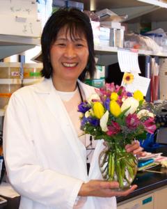 Noriko Steiner holds a vase of flowers