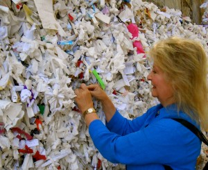 Inserting a wish for a blessing into the 'wishing wall'